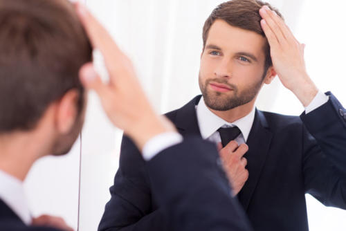 Making sure he looks perfect. Handsome young man in formalwear adjusting his hairstyle and smiling while standing against mirror