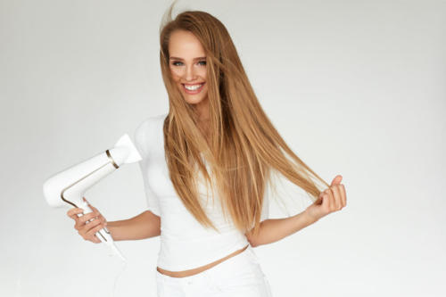 Hair Dryer. Woman Drying Beautiful Blonde Long Straight Hair