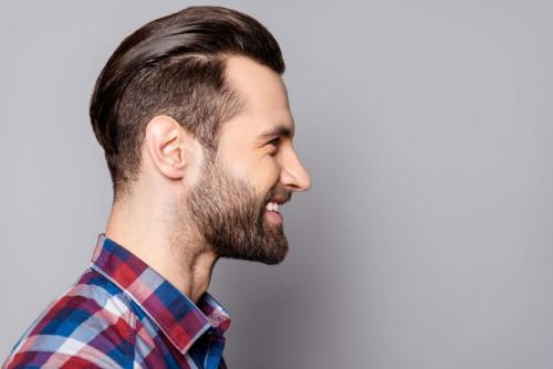 A side view portrait of young handsome smiling man with stylish