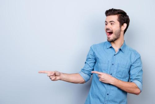 Portrait of young stylish guy in jeans shirt, pointing on copysp