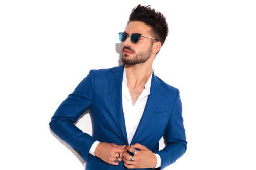elegant man wearing sunglasses buttoning his suit and looks away