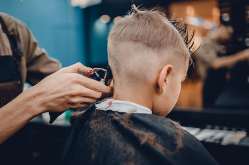 Barber shop. Barbershop Hairdresser makes hairstyle a man with a beard child
